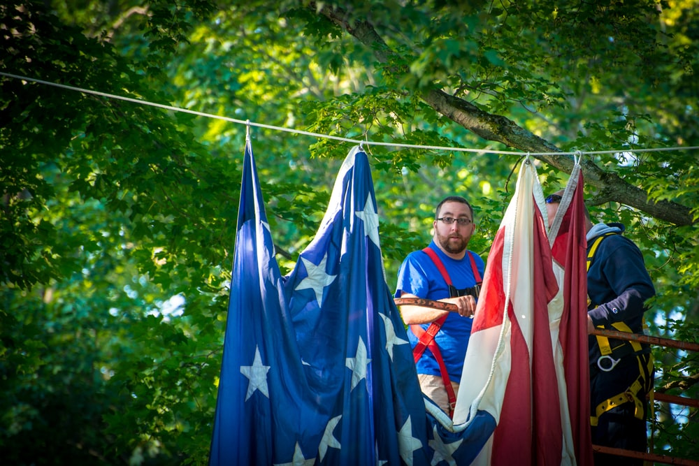 man standing near hanging red and blue textile