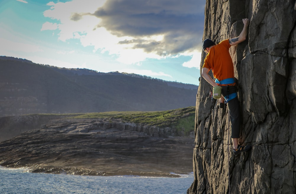 person climbing on rock formation during daytime
