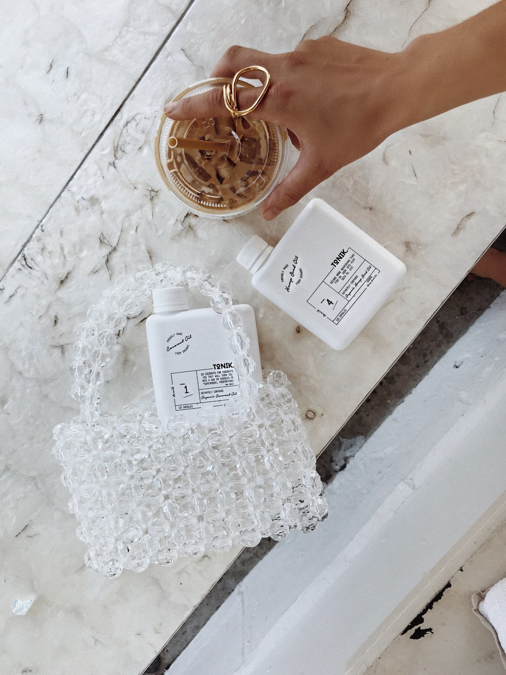 white beaded bag with two white plastic containers