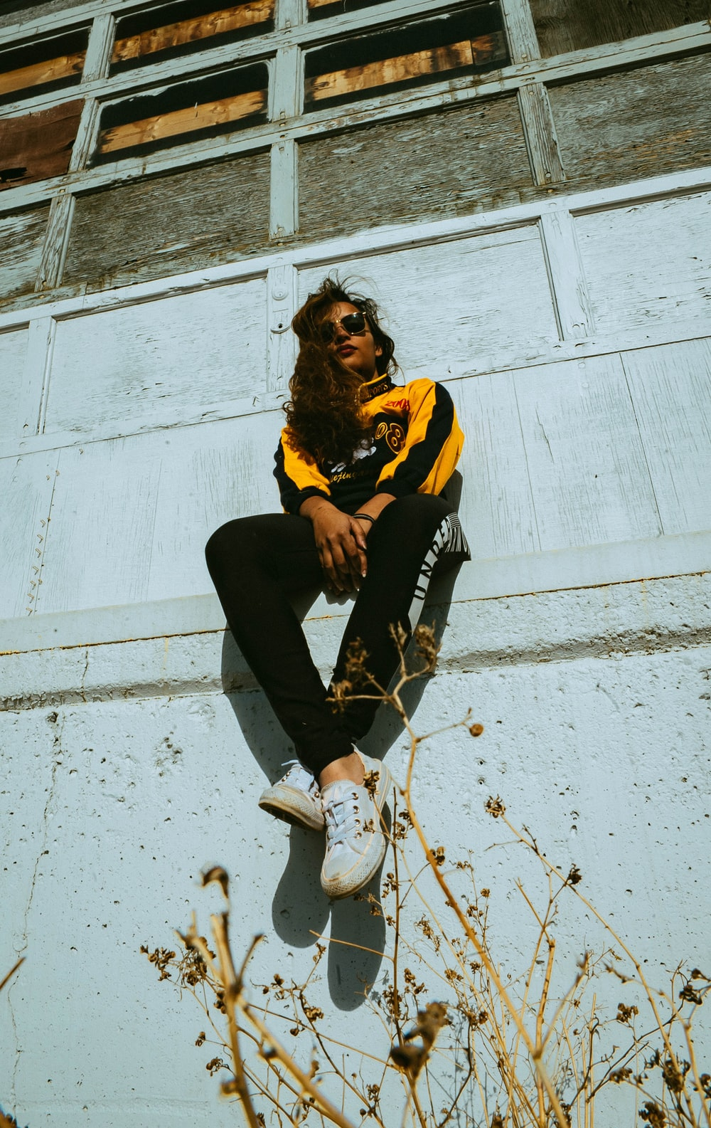 woman wearing black and yellow track suit while sitting
