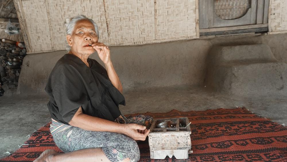 woman sitting on area rug