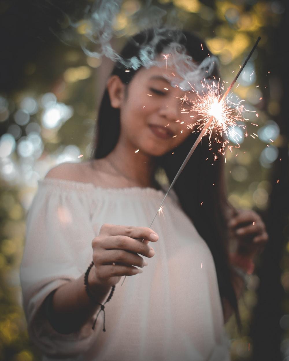 woman wearing white off-shoulder top holding sparkler