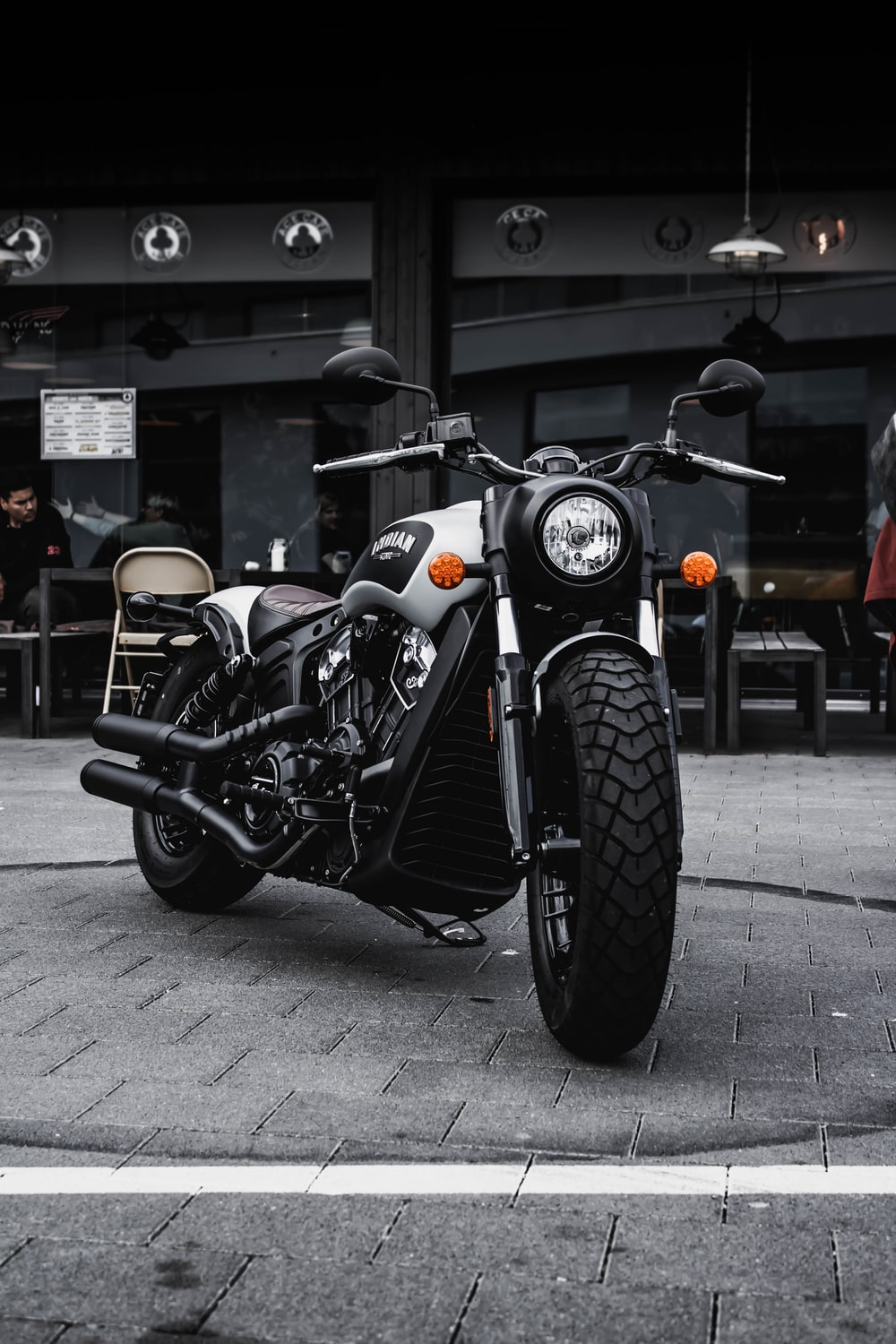 black and gray cruiser motorcycle parked beside black concrete building