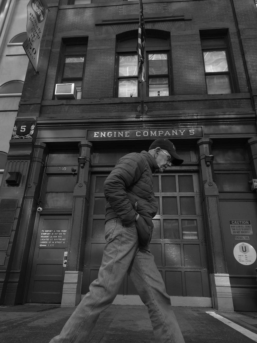 greyscale photo of man walking near Engine Company building