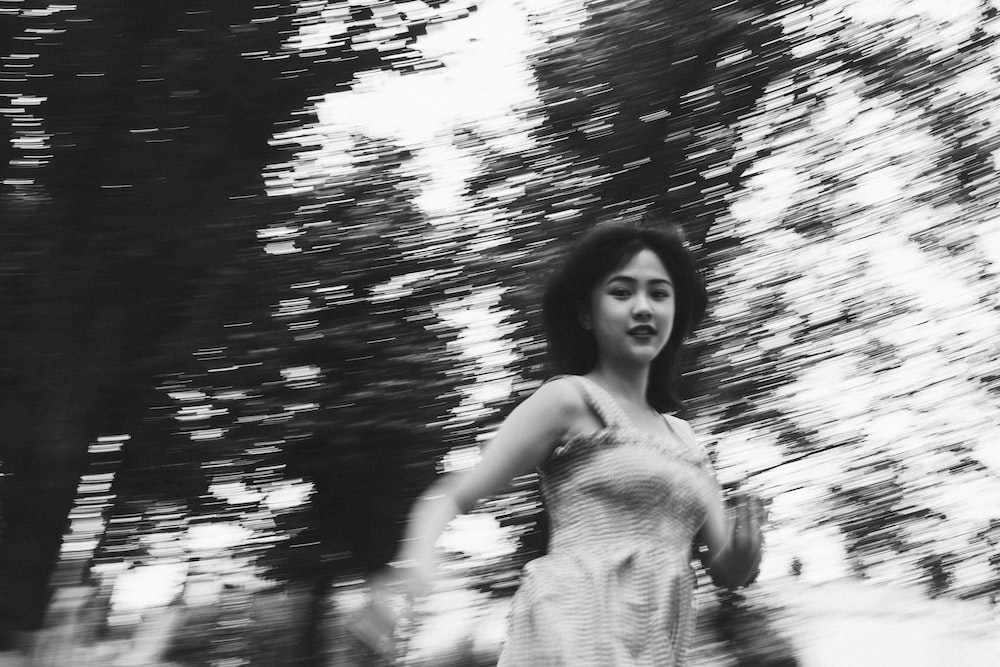 grayscale photography of woman surrounded by trees