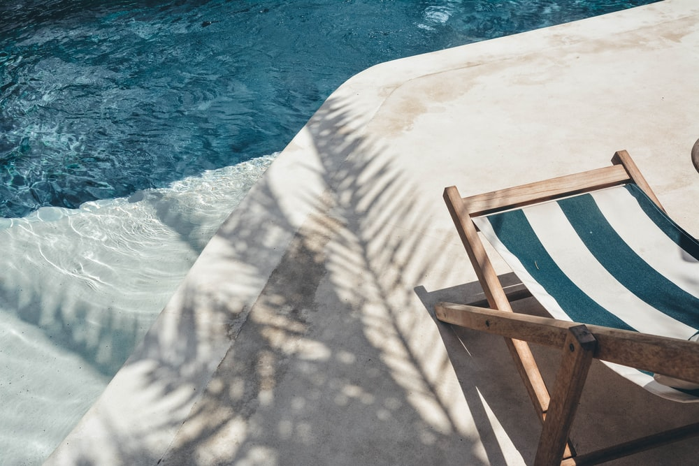 brown wooden lounger near body of water