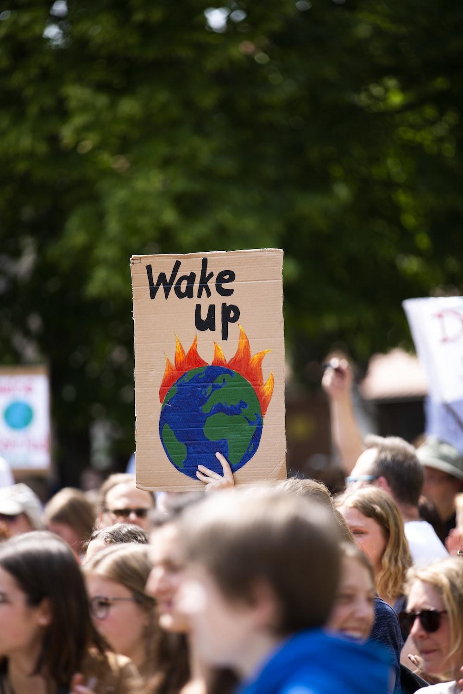person holding wake up signage