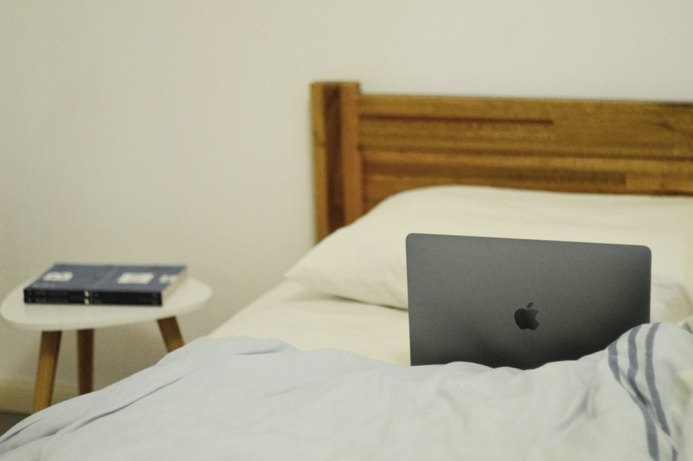 silver MacBook on bed in room