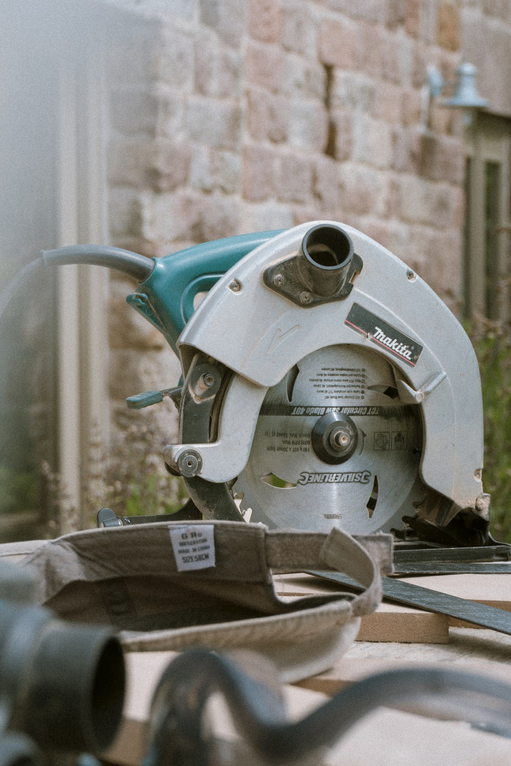 grey and teal Makita miter saw on table outdoors during daytime