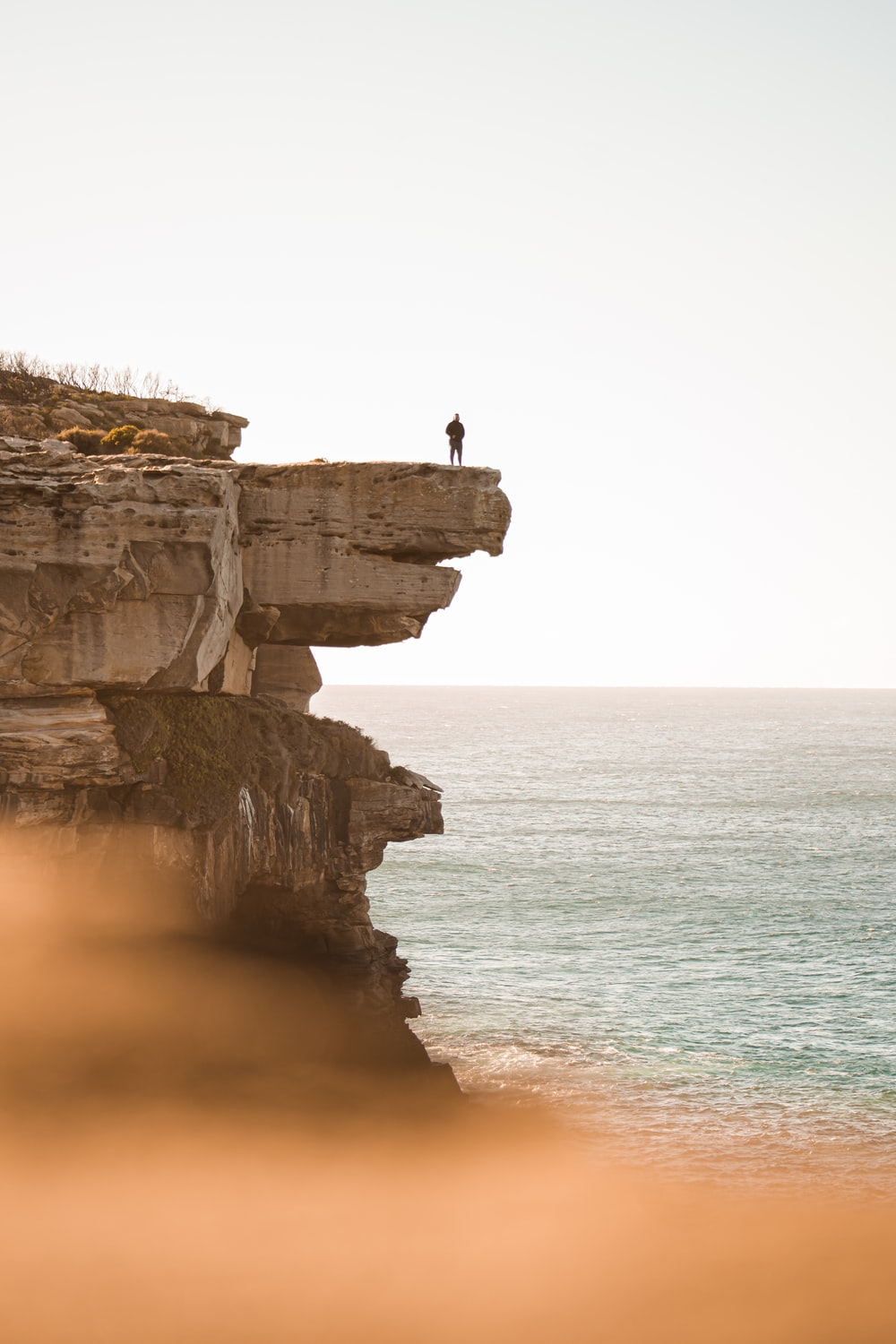 person standing on rocky cliff near body of water during daytime