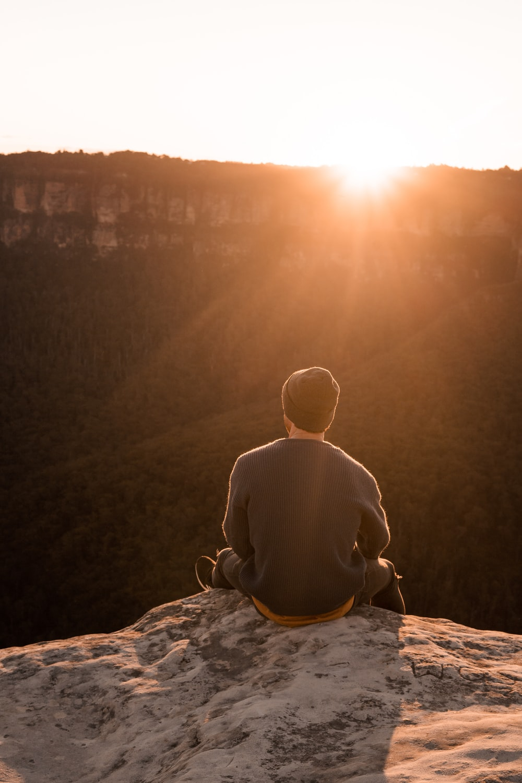 man in bonnet sitting on top of mountain