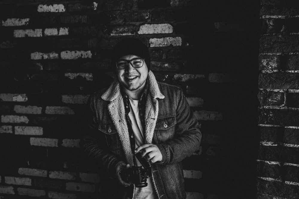 grayscale photography of smiling man carrying camera