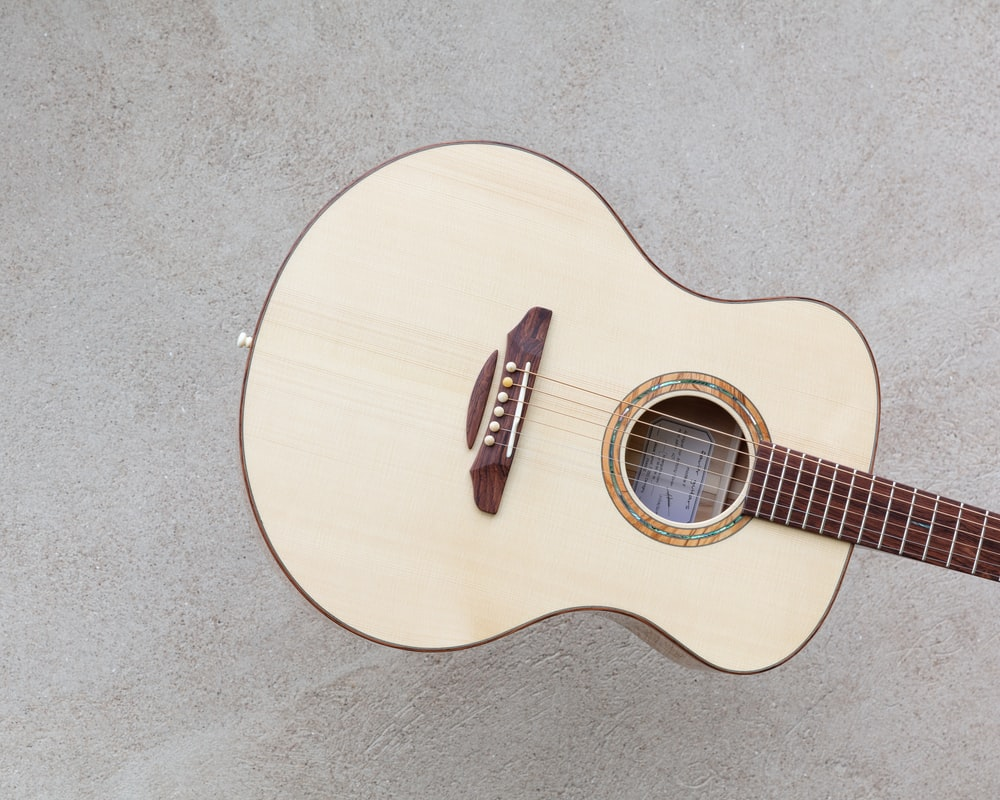 white and brown wooden dreadnought guitar
