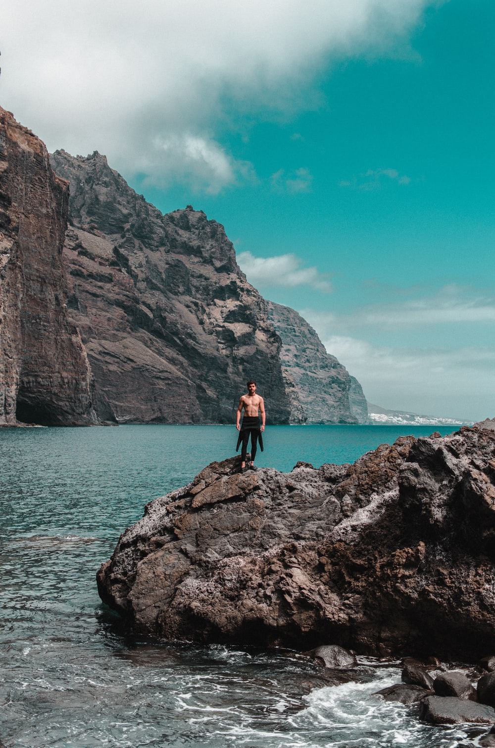topless man standing on rock formation near ocean during daytime