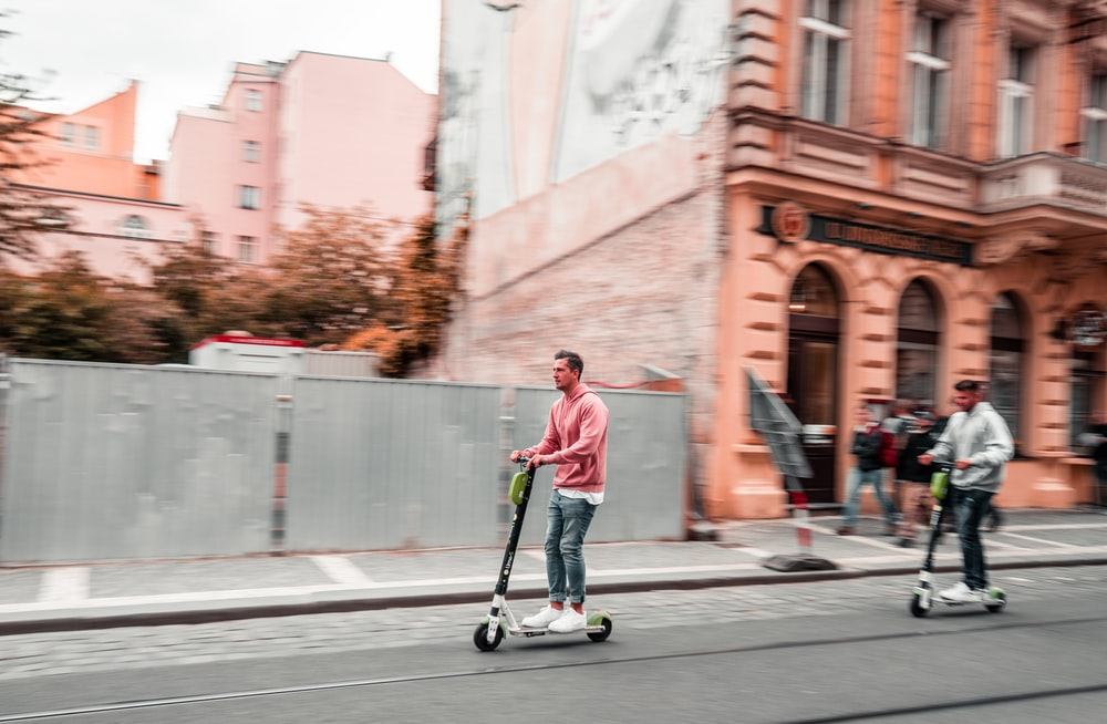 two men riding kick scooters during daytime