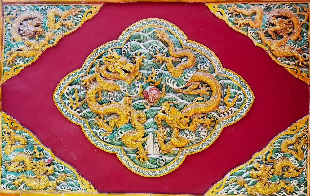 yellow, beige, and red dragon print textile