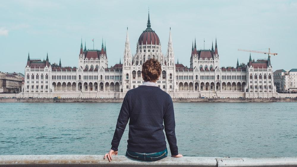 person sitting on gray concrete railings