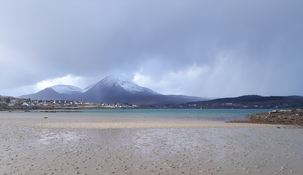 seashore with snow-covered mountain under grey clouds
