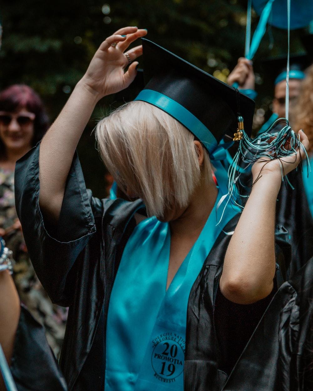 woman wearing blue and black graduation coat