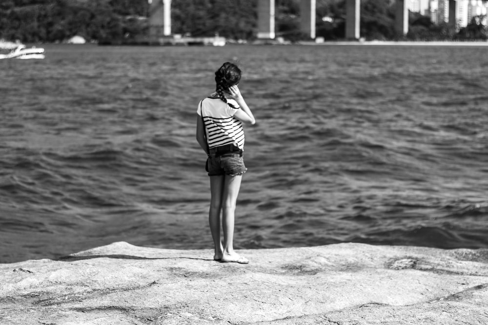 grayscale photography of girl standing near body of water