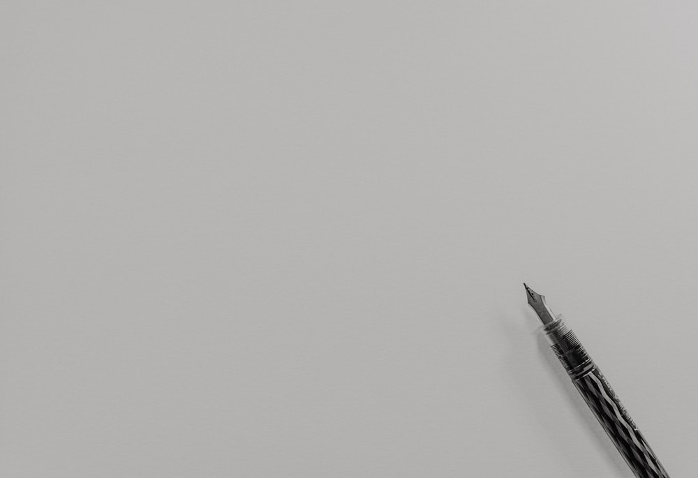 grayscale photo of fountain pen