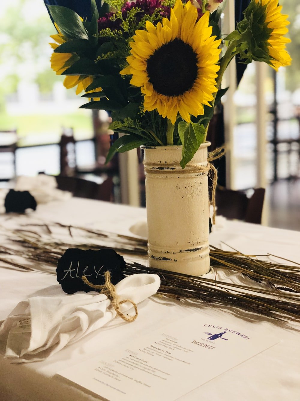 yellow sunflower in vase on top of table
