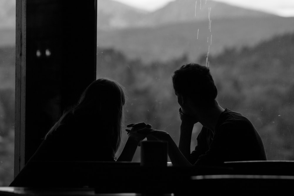 grayscale photography of couple sits by the window