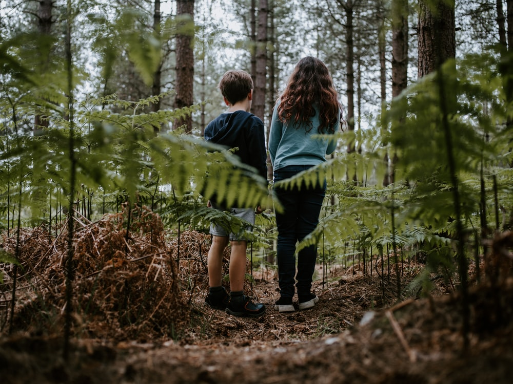 girl and boy standing side by side at the woods