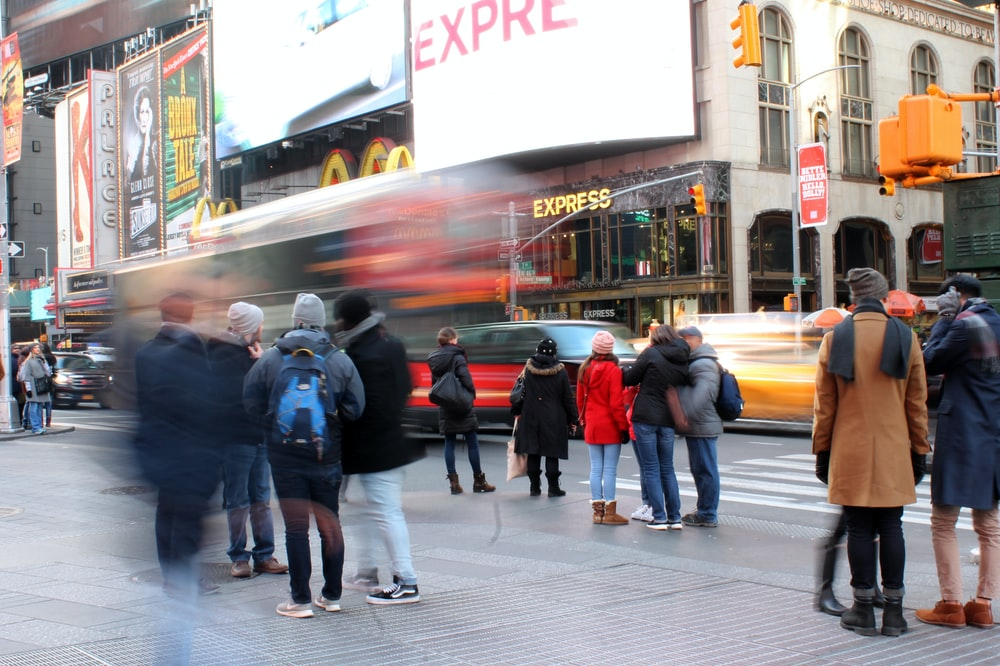 people standing at sidewalk along busy street
