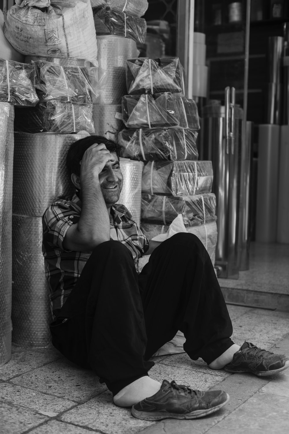 grayscale photography of man sitting on floor