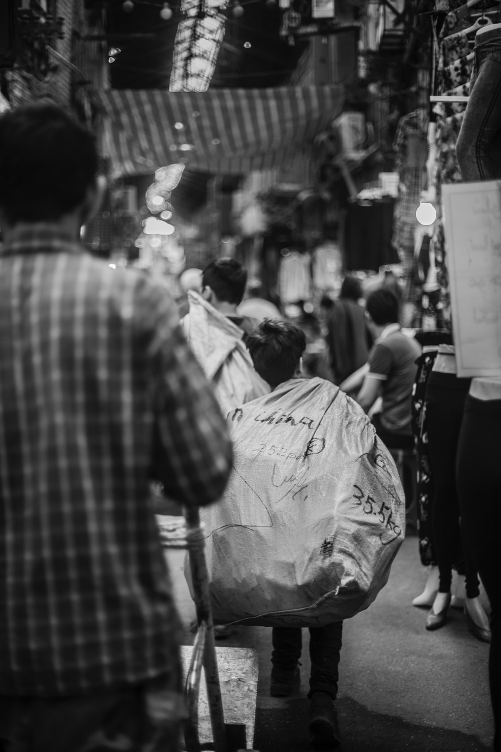 grayscale photography of boy carrying sack while walking