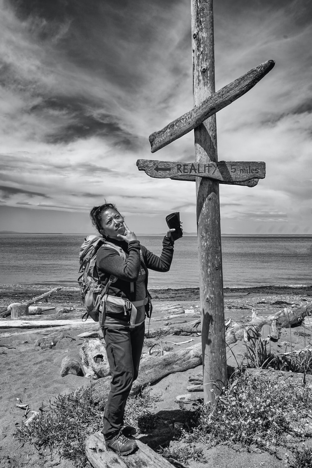 grayscale photo of woman standing beside post