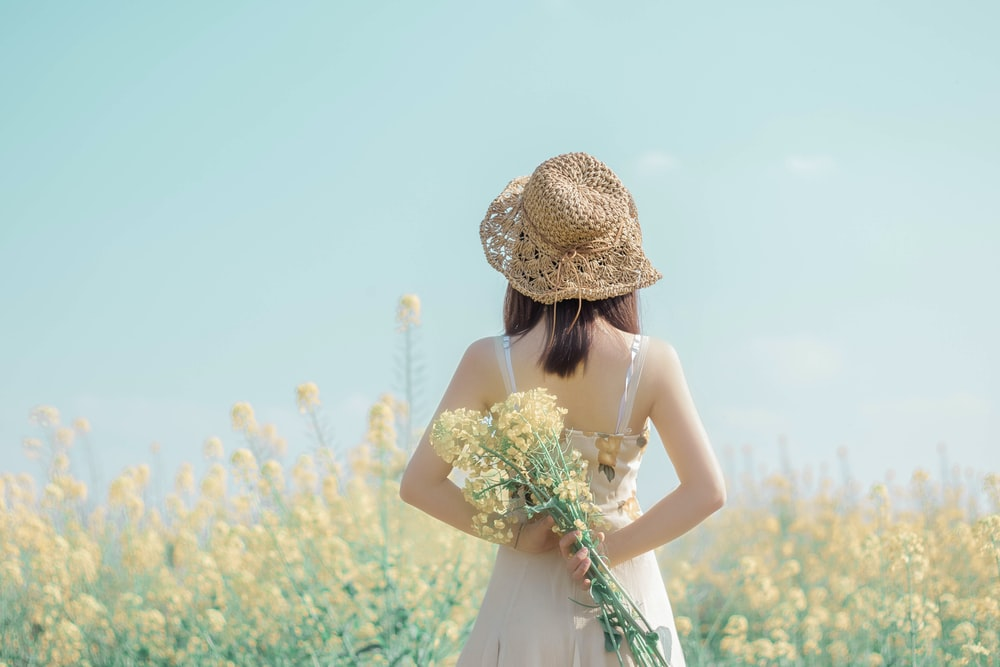 woman in white dress carrying flowers