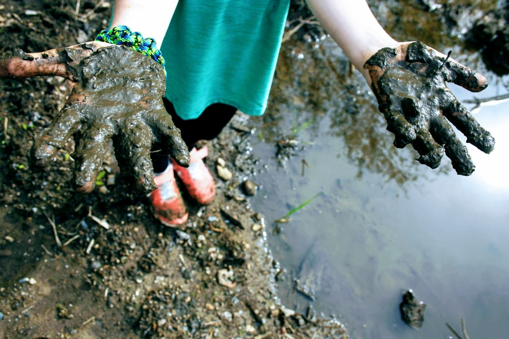 child in green top with mud on hand