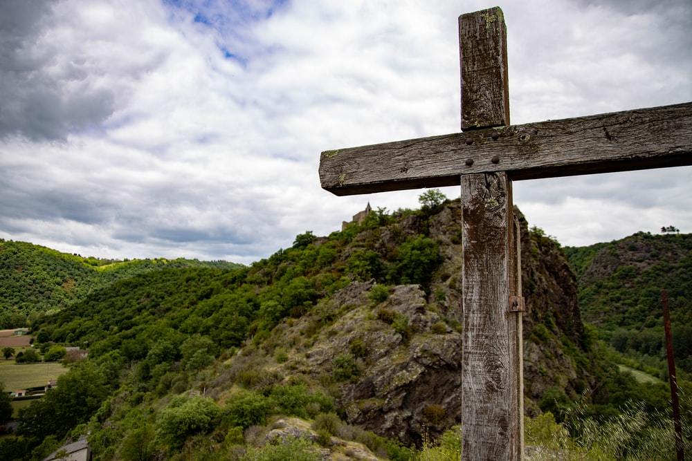 view of green hill from brown wooden cross