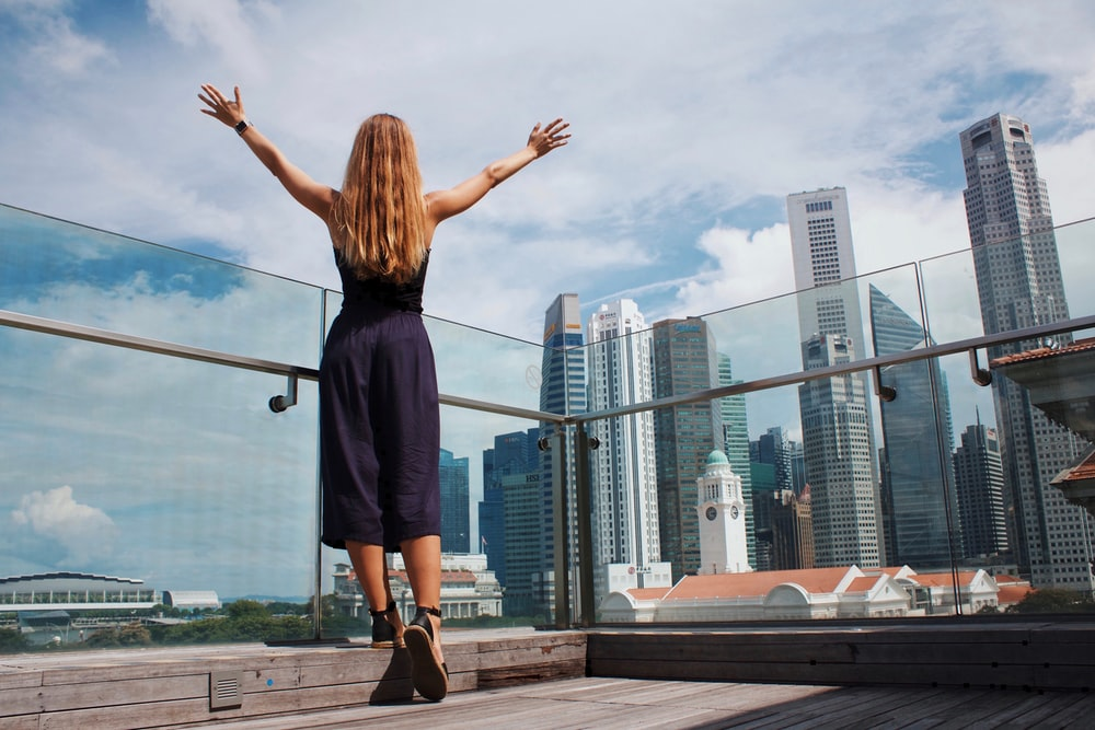 woman raising her hands while standing near glass wall