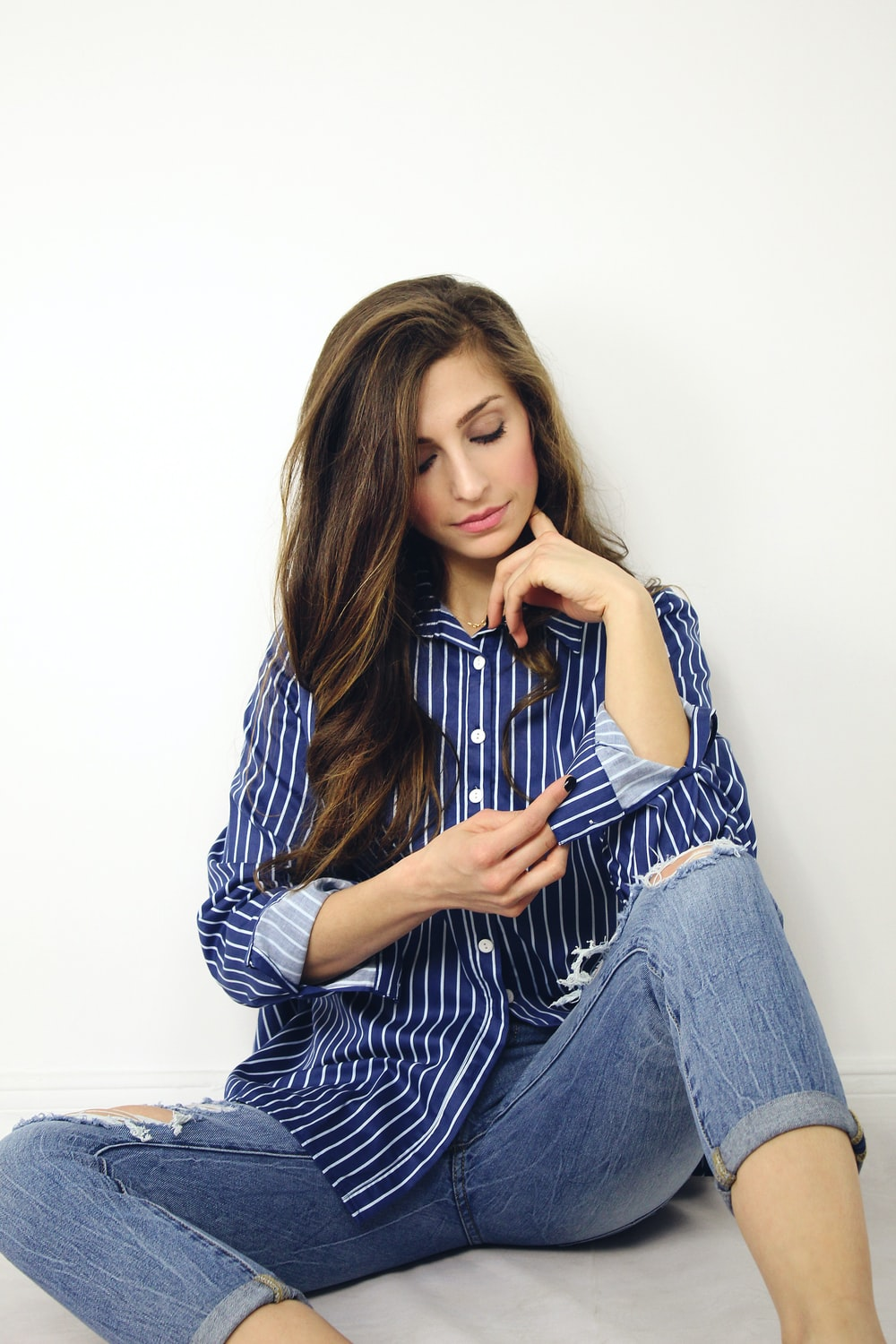 woman wearing blue and white striped dress shirt and blue denim jeans sitting on gray surface