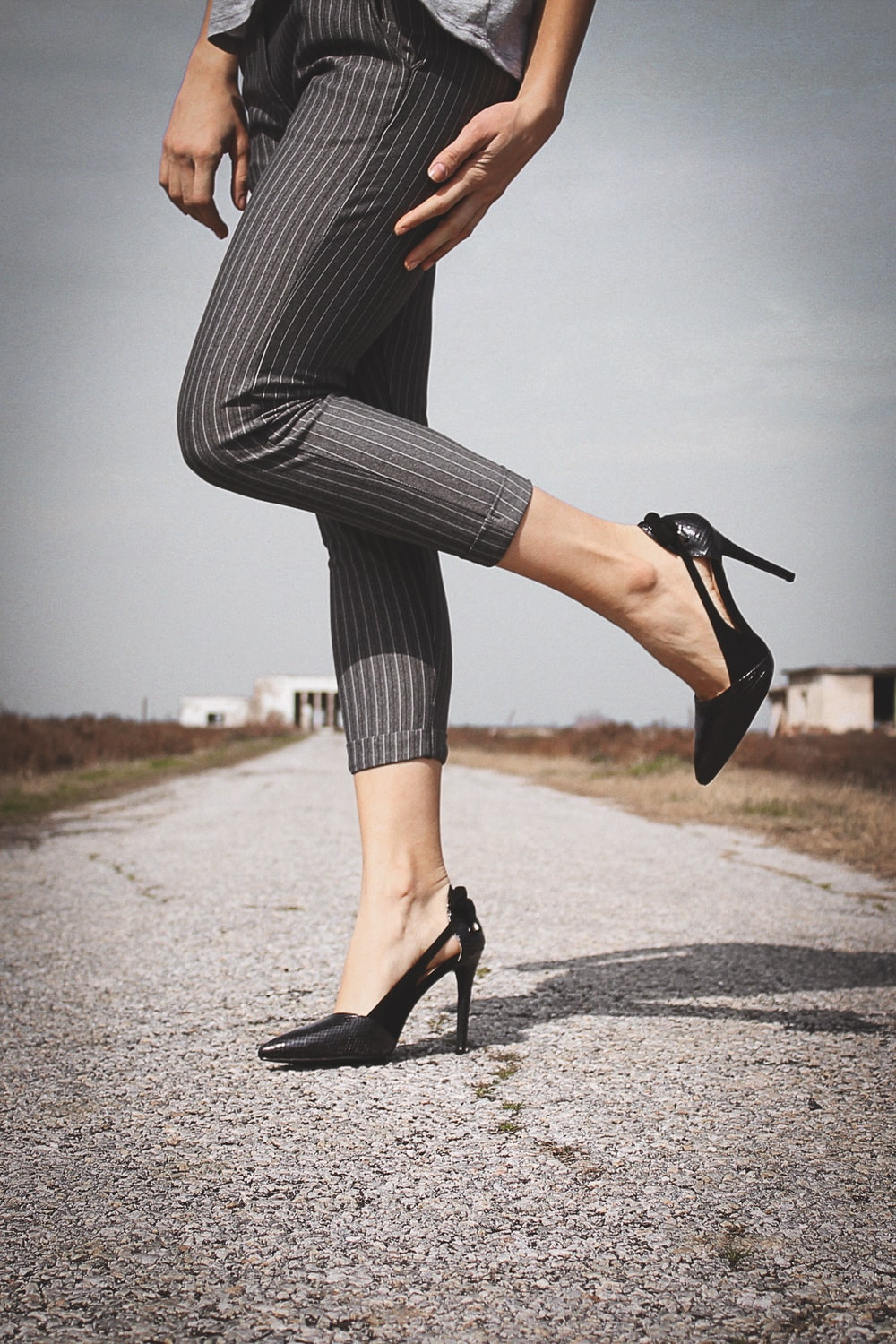woman standing while wearing black leather heeled sandals