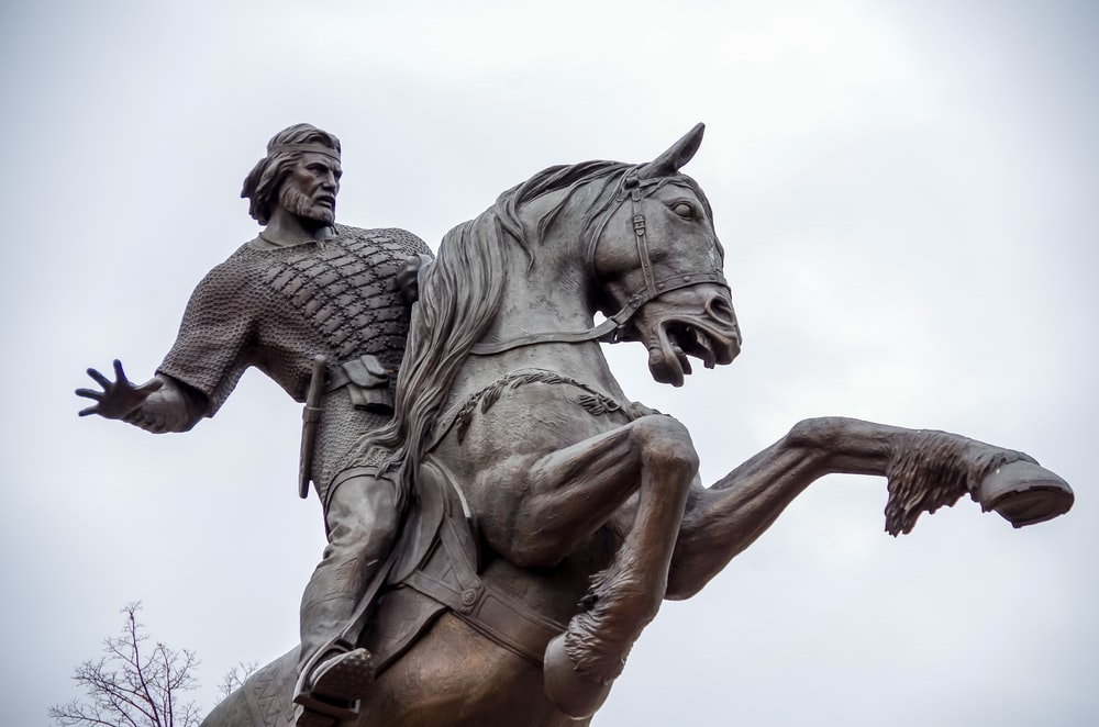 selective focus photography of man riding horse statue