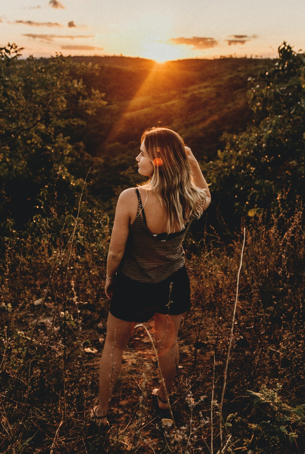 woman standing in green grass during golden hour