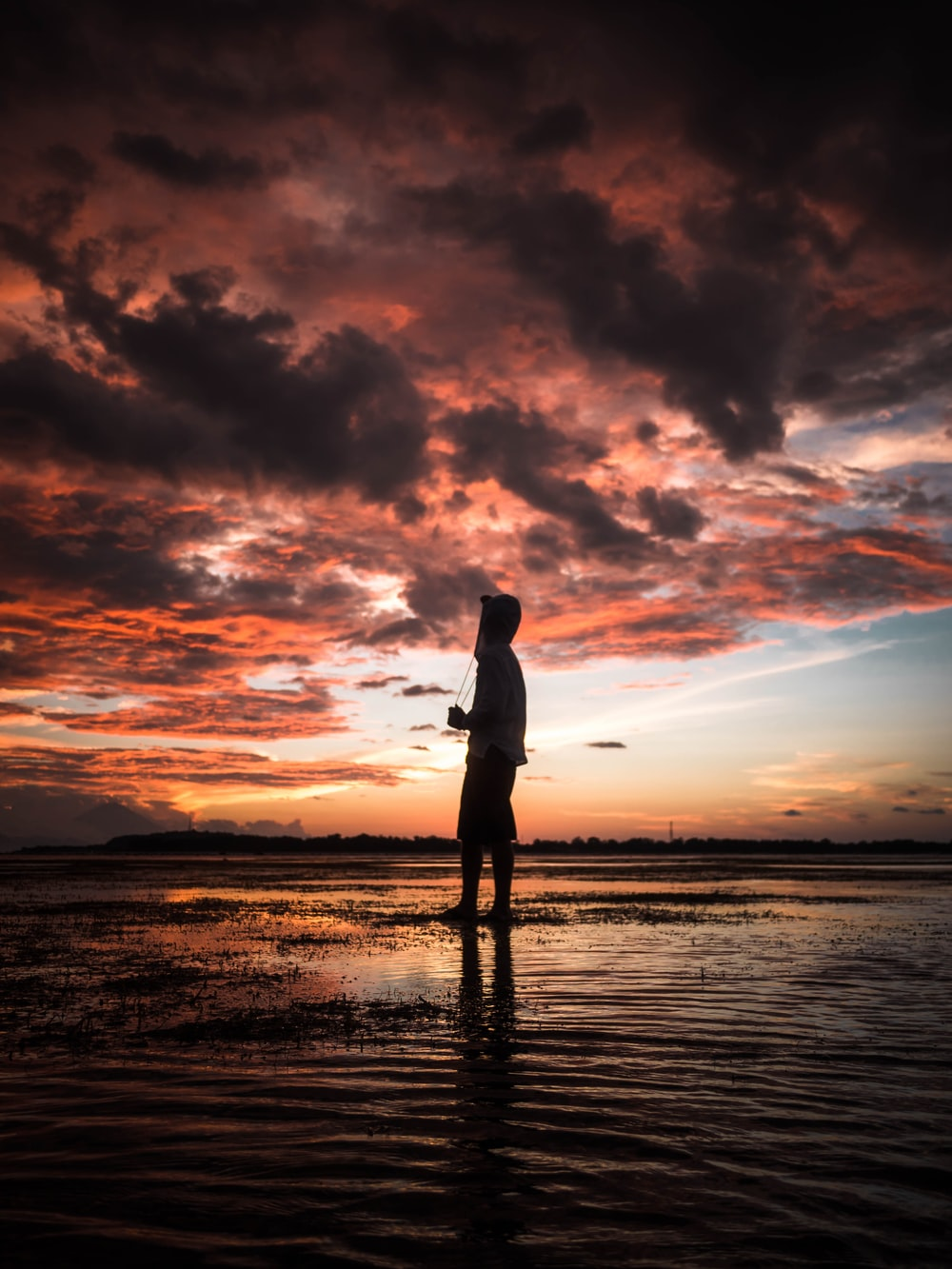 man standing in seashore during sunset