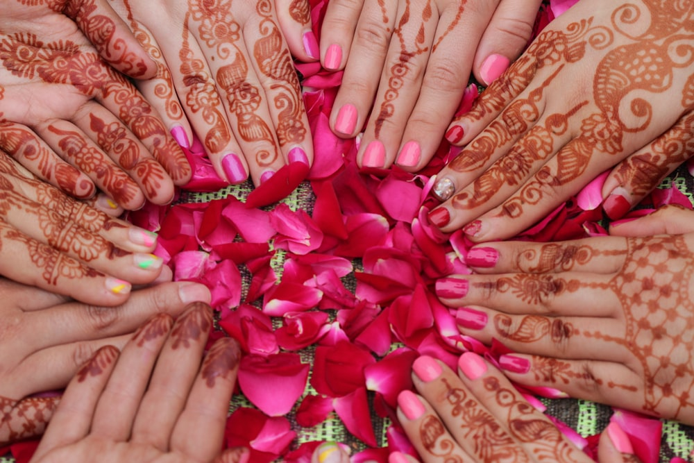 red flower petals surrounded by hands with mhendi tattoos