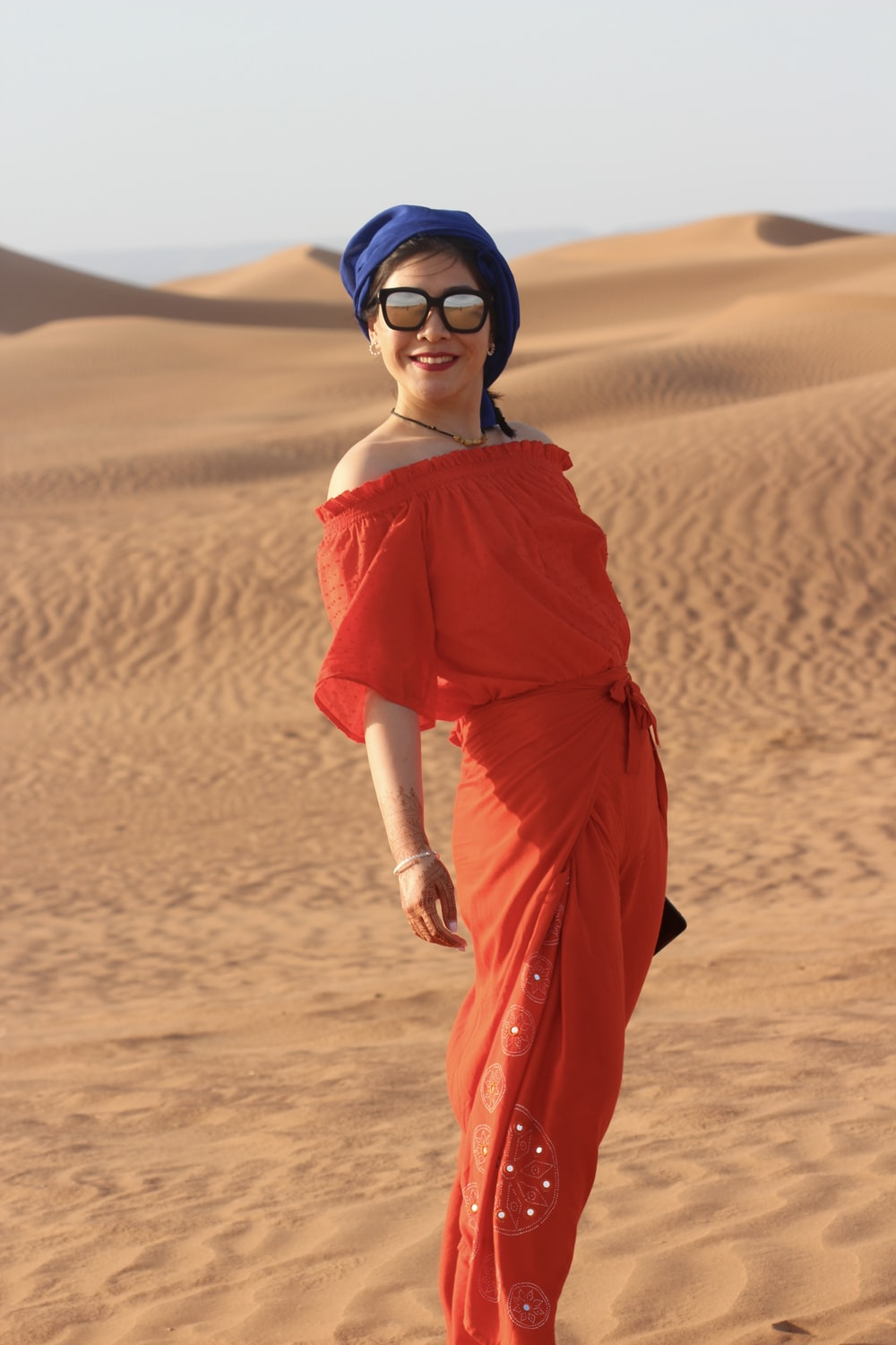 standing woman in red dress at sand dunes during daytime
