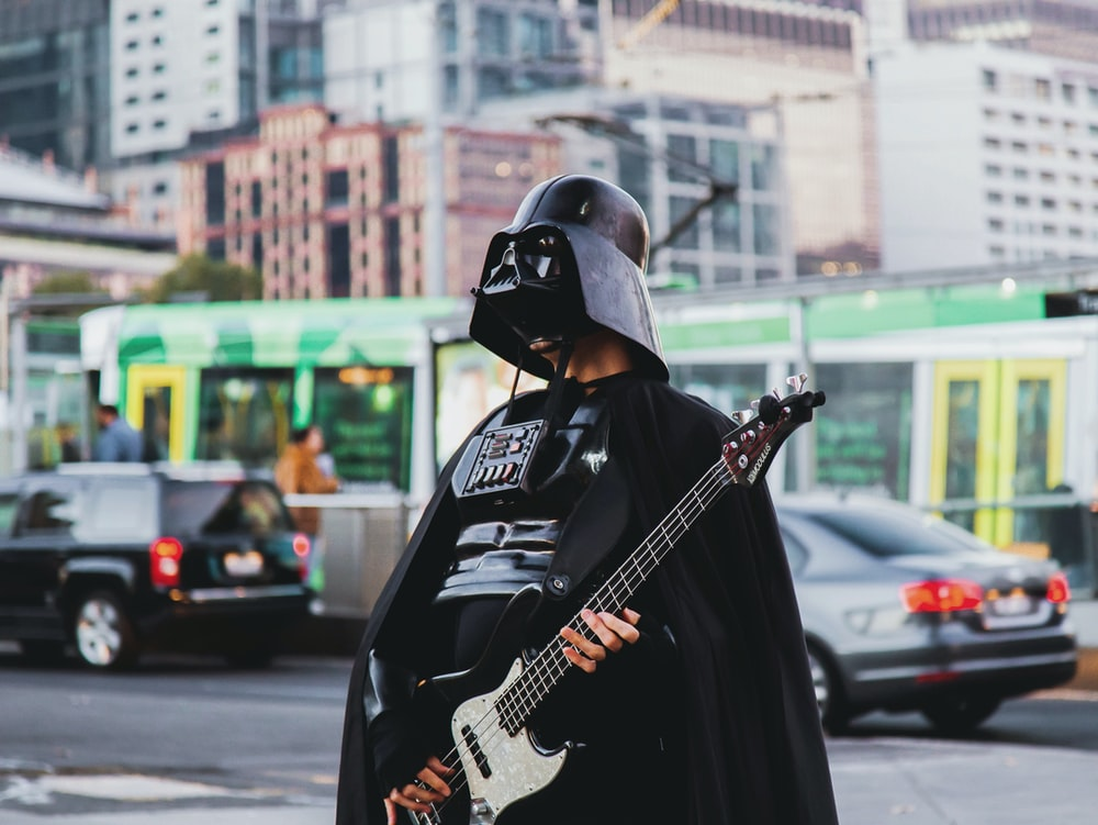 person in Darth Vader costume holding guitar