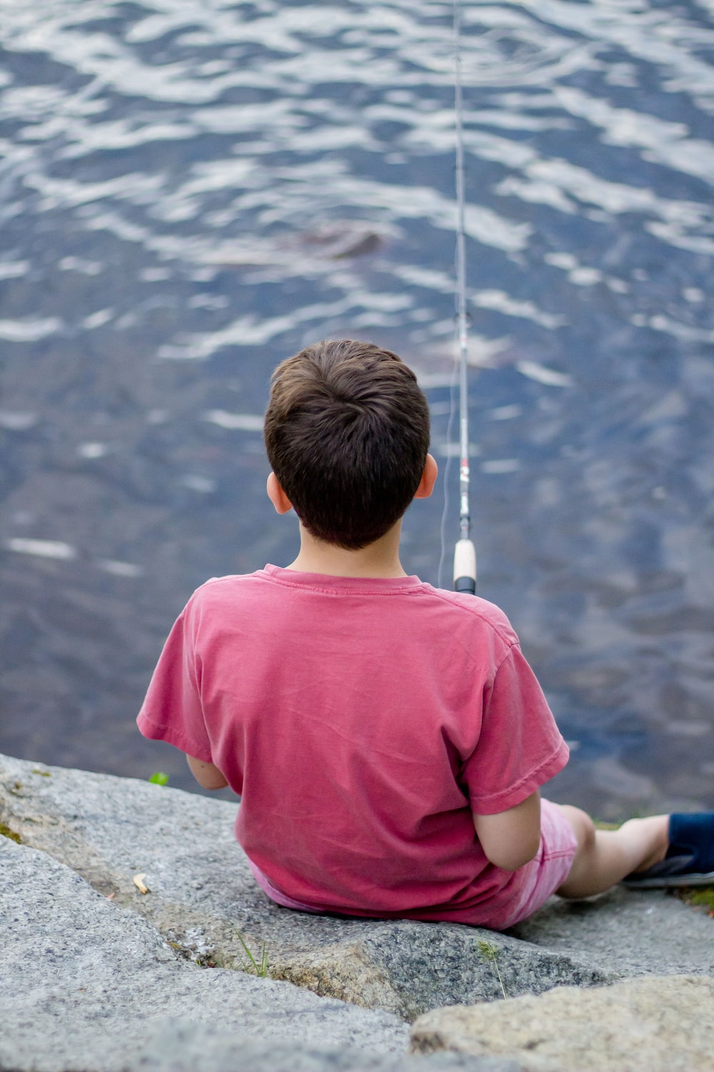 boy fishing on body of water
