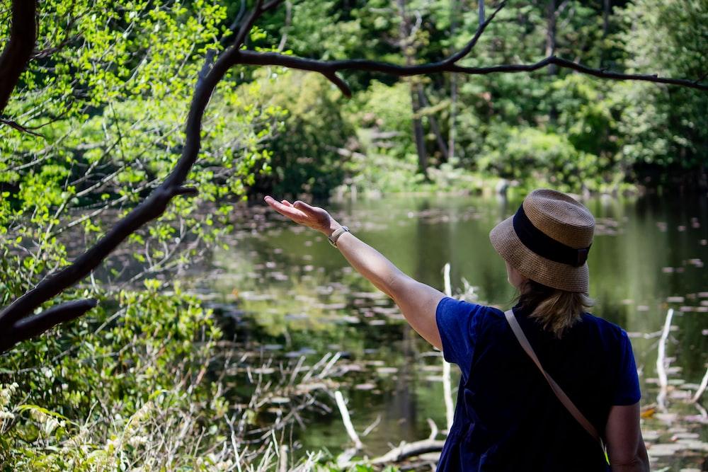 woman standing beside water under green tree