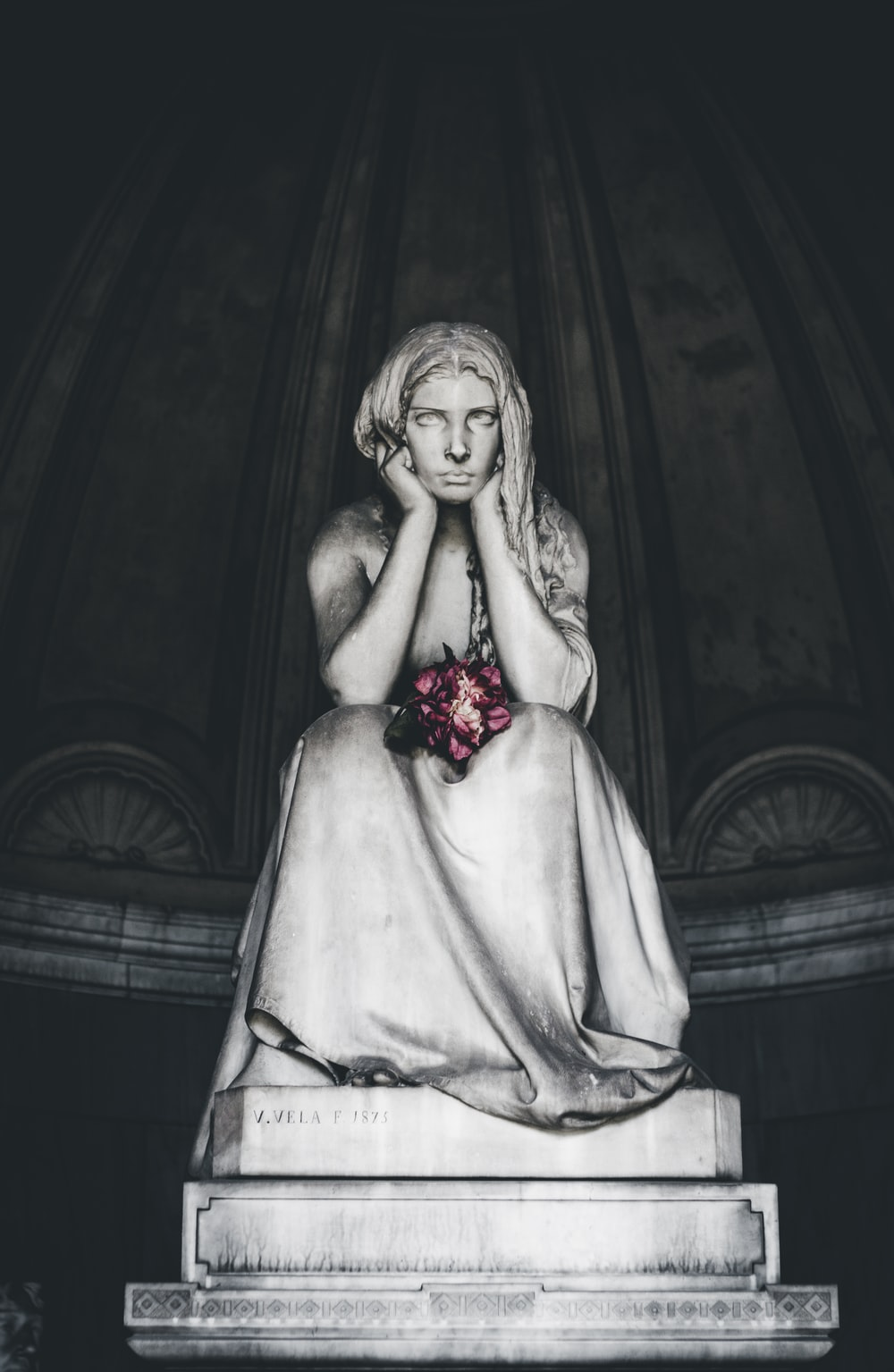 woman sitting head resting on hands statue