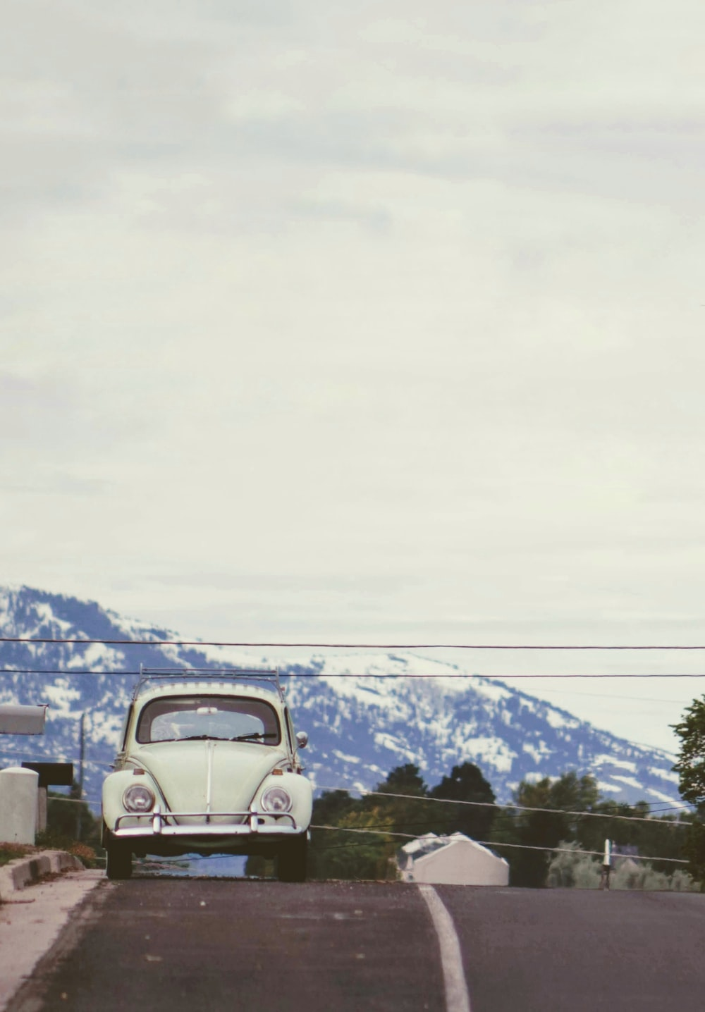 classic white Volkswagen beetle coupe at road