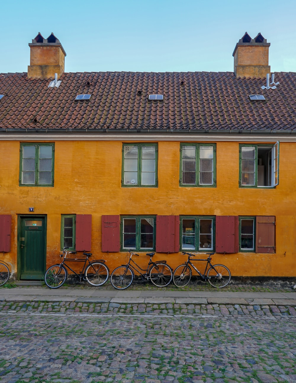 three bicycle leaning on house