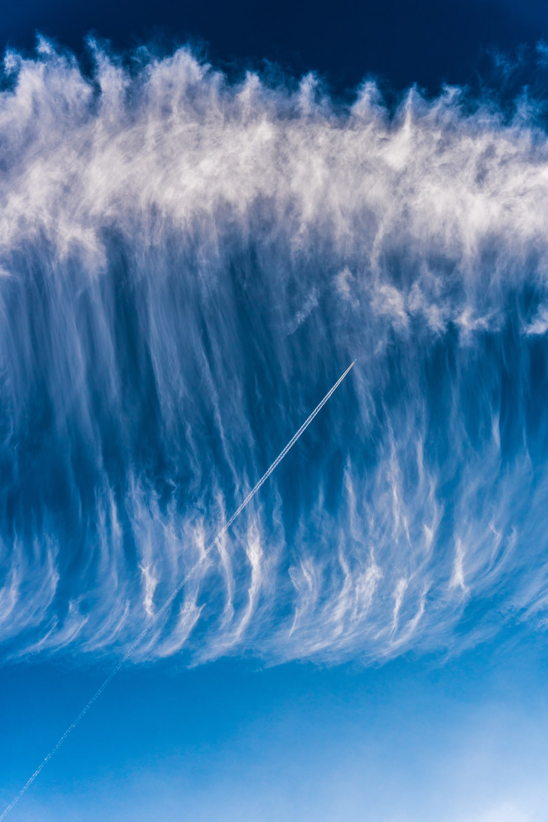 Sky surfing - Airplane skytrail (contrail) in a wave of clouds